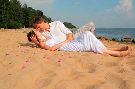 Foto de couple kissing while lying on the shore - Imagen libre de derechos