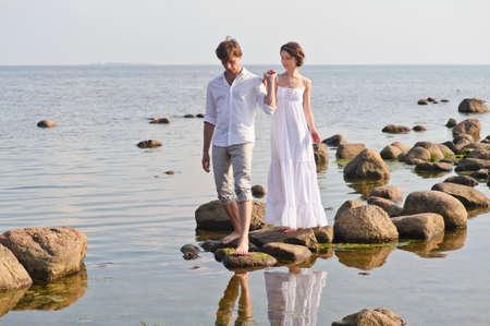 Foto de young romantic pair walks at water - Imagen libre de derechos