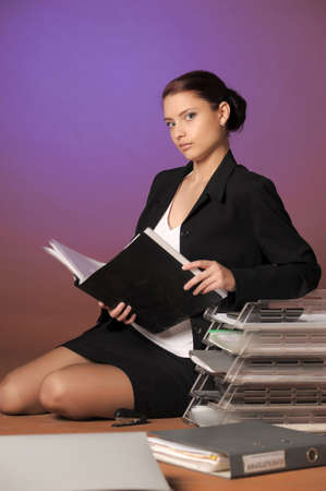 Young secretary or businesswoman in suit with notebook