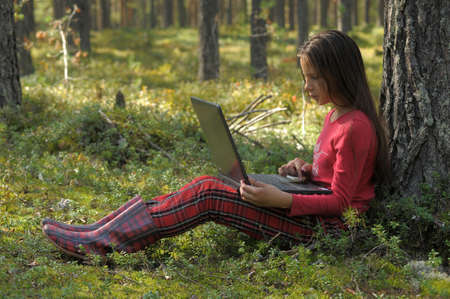 girl with laptop in the woods