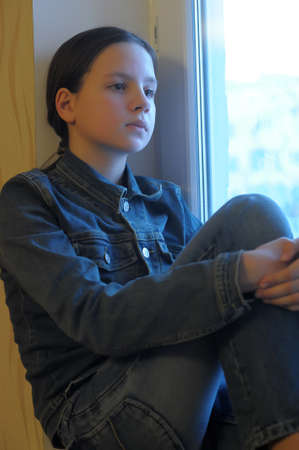 The sad girl the teenager at home on a window sill