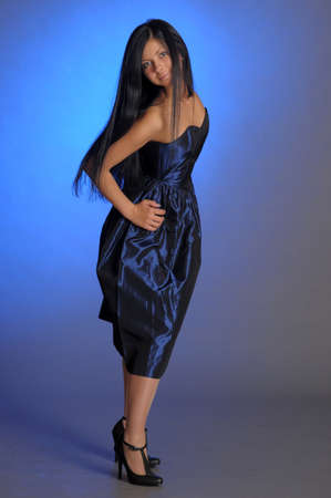 dramatic dark-haired girl in a blue dress