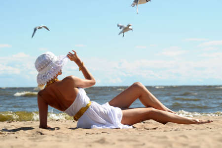 the girl in a dress and hat on the beach