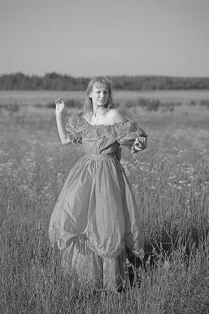young woman in an old dress in the middle of the field