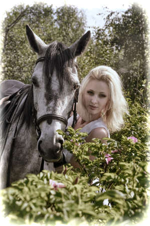 blonde with a horse among the bushes of a blooming rose hips