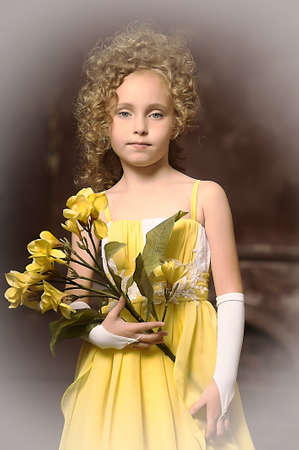 Girl in a yellow dress with a flower in hand