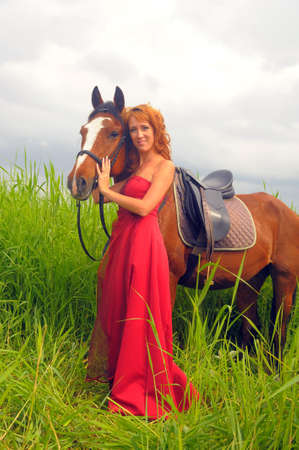 beautiful woman in a red dress with a horse