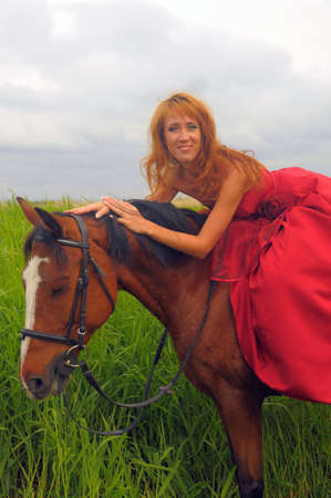young beautiful woman in a red dress on a horse