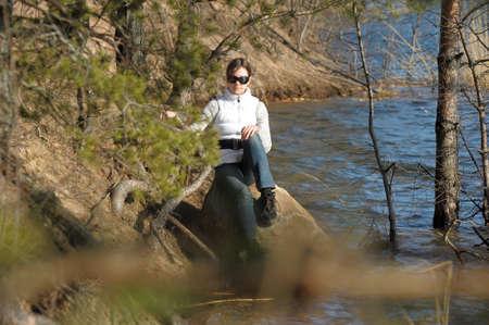 teen girl sitting on a rock near the water