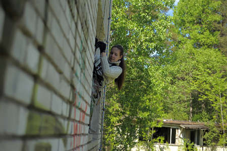 Girl hangs from a building on the climbing equipment, Summer training camp for teen, Russia.