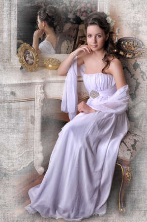 Exquisite elegant girl in white dress sitting on a chair near the mirror.