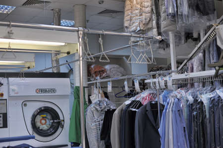 Reception point of dry cleaning, lot of clean clothes in pack. Auchan, St. Petersburg, Russia.