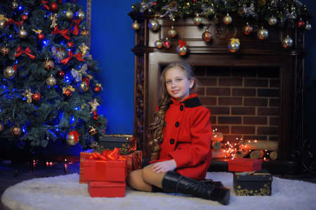 Christmas girl in a red coat against the background of a fireplace with the lights.