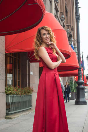 Beautiful elegant woman in a red dress on the street.