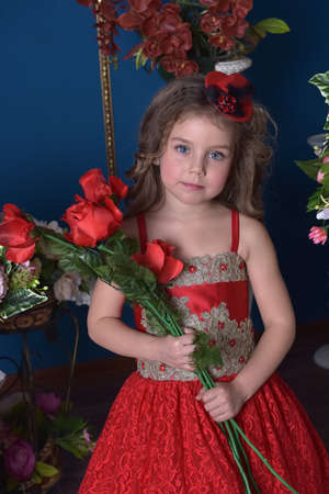 portrait of a little princess girl in a red dress with flowers in her hands and around her