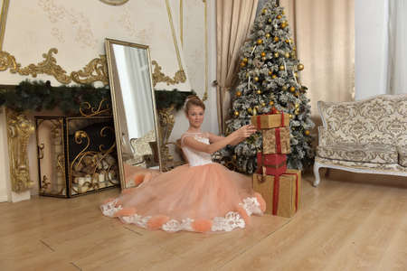 Foto de beautiful young girl with evening hairstyle in pink with white dress in christmas,, tree with gold ornaments - Imagen libre de derechos