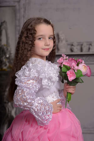 Photo for beautiful cute girl princess with curly hair and flowers in her arms, brunette with long hair, a child - Royalty Free Image