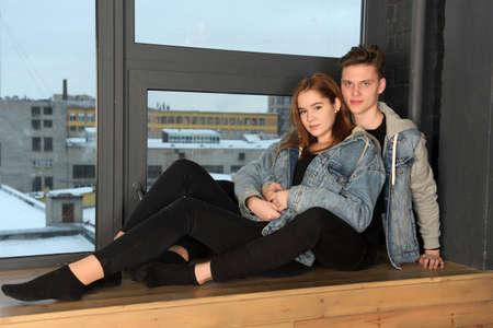 Photo pour young couple in love with denim jacket sitting hugging - image libre de droit