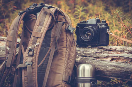 Lifestyle hiking camping equipment retro photo camera backpack and outdoor forest nature on background