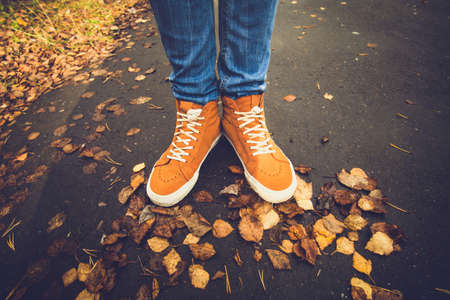 Photo pour Feet sneakers walking on fall leaves Outdoor with Autumn season nature on background Lifestyle Fashion trendy style - image libre de droit