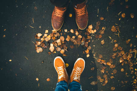 Couple Man and Woman Feet in Love Romantic Outdoor with Autumn leaves on background Lifestyle Fashion concept