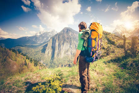 Foto de Young Man Traveler with backpack relaxing outdoor with rocky mountains on background Summer vacations and Lifestyle hiking concept - Imagen libre de derechos