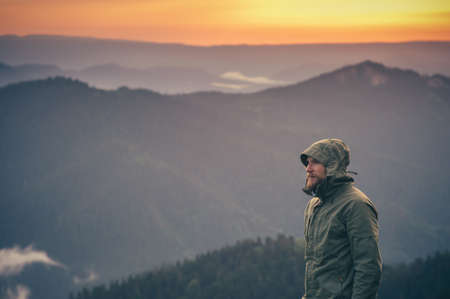 Foto de Young Man bearded standing alone outdoor with sunset mountains on background Travel Lifestyle and survival concept - Imagen libre de derechos