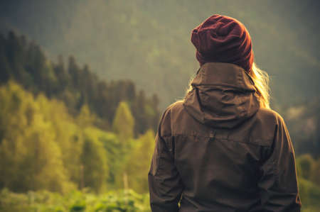 Photo pour Young Woman standing alone outdoor with wild forest mountains on background Travel Lifestyle and survival concept rear view - image libre de droit