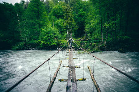 Man Traveler hiking on wooden bridge over river Travel Lifestyle concept Summer journey vacations outdoor