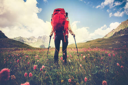 Foto de Woman Traveler with red backpack hiking Travel Lifestyle concept Summer vacations outdoor mountains and flowers valley on background - Imagen libre de derechos