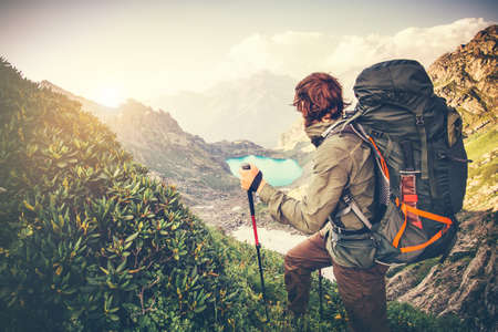 Foto de Man Traveler with big backpack mountaineering Travel Lifestyle concept lake and mountains on background Summer extreme vacations outdoor - Imagen libre de derechos
