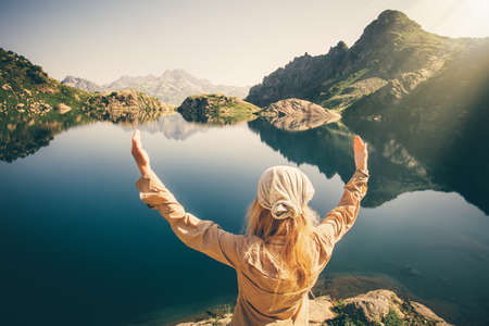 Foto de Woman Traveler meditating harmony with nature Travel healthy Lifestyle concept lake and rocky mountains landscape on background outdoor - Imagen libre de derechos