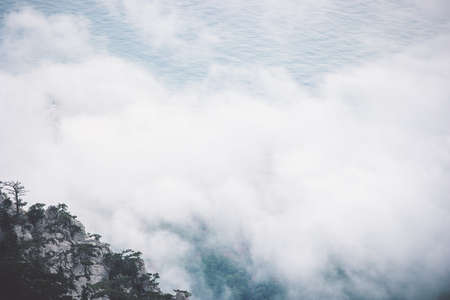 Clouds Foggy Mountains cliff and sea Landscape minimalistic style Travel serene scenic aerial view moody weather