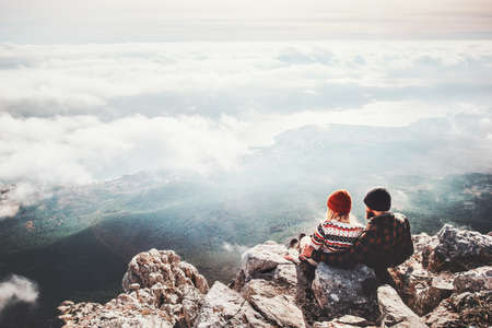 Photo pour Couple travelers Man and Woman sitting on cliff relaxing mountains and clouds aerial view  Love and Travel happy emotions Lifestyle concept. Young family traveling active adventure vacations - image libre de droit