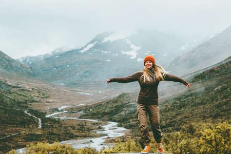 Woman bliss emotional raised hands foggy mountains on background Travel Lifestyle wellness concept adventure  vacations outdoor harmony with nature Jotunheimen park in Norway