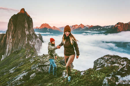 Photo pour Happy Couple holding hands traveling together hiking in Norway healthy lifestyle concept active vacations outdoor Segla mountain sunset landscape - image libre de droit