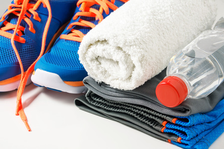 Fitness gym accessories with sport clothing towel drinking water and running shoes