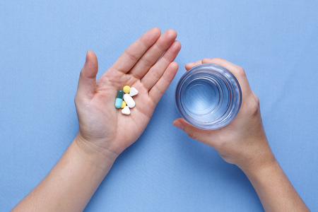 Taking pill with hand holding pills and glass of water