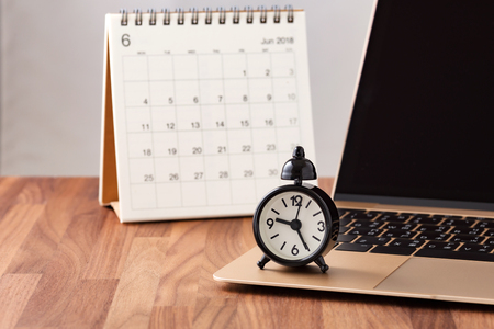 Time management concept with calendar and clock on computer on wooden table
