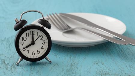 Foto de Intermittent fasting concept with clock, white plate, fork and knife on blue table - Imagen libre de derechos