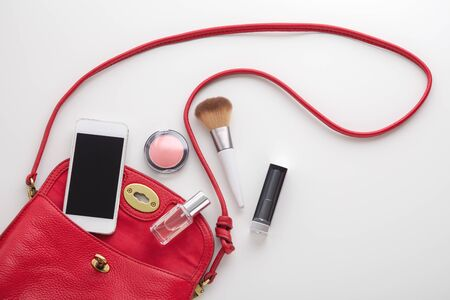 Photo pour Red woman fashion bag with lipstick, blush, perfume and smartphone on white background, top view - image libre de droit