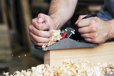 Close-up as a carpenter carpenter builder handles a wooden plank board jack plane  in the workshop