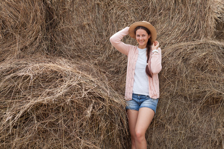 Young beautiful woman with dark hair in straw hat, pink cardigan, denim shorts smiling and beautifully posing against the background of large straw stacks of hay in a summer day in the village