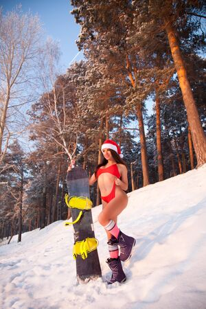 Woman fitness model in a red swimsuit, Santa Claus cap, snowboard boots smiling, stands on a snowboard and attractively poses on a ski slope in winter, in the background a coniferous forest