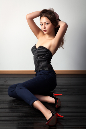 Foto de Asian young woman  in black top and classic black pants posing and sitting on a  black wooden floor against a white wall background  - Imagen libre de derechos