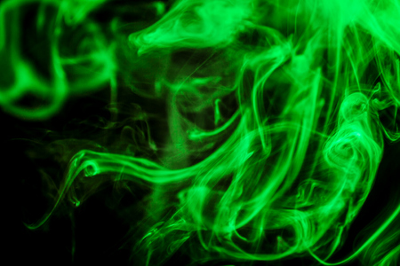 Thick colorful smoke of green on a black isolated background. Background from the smoke of vape