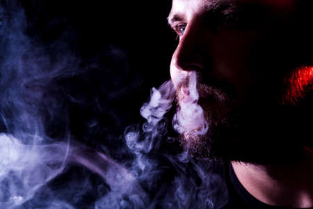 A young man exhales a cloud of colored smoke of red and blue color on a black isolated. Harm to smoking on the example of a young mugger