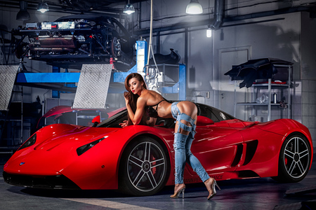 Novosibirsk, Russia - August 16, 2018: Young woman fitness model in jeans and a swimsuit posing for advertising a sports car of a supercar Marussia in a car salon