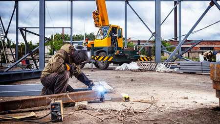 Photo pour A strong man is a welder in brown uniform, welding mask and welders leathers, a metal product is welded with a arc welding machine at the construction site, blue sparks fly to the sides - image libre de droit