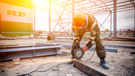 Photo for A strong  man welder in brown uniform, a construction helmet and welders leathers, grinder metal an angle grinder  at the construction site, orange sparks fly to the sides - Royalty Free Image